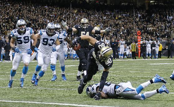 New Orleans Saints tight end Jimmy Graham (80) scores on a touchdown as Carolina Panthers cornerback Drayton Florence tries to tackle in the second half of an NFL football game in New Orleans, Sunday, Dec. 8, 2013