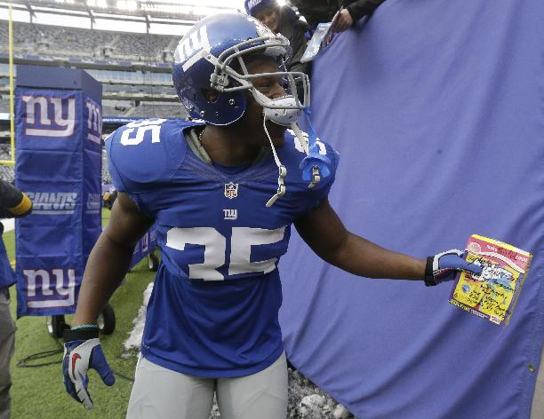 New York Giants running back Andre Brown holds a gift from Joe Vostal, of Summit, N.J., which was given to him for his birthday before an NFL football game against the Seattle Seahawks, Sunday, Dec. 15, 2013, in East Rutherford, N.J. Brown turned 27 on Sunday