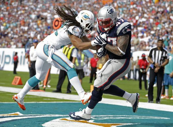 New England Patriots tight end Michael Hoomanawanui (47) grabs a touchdown pass as Miami Dolphins outside linebacker Philip Wheeler (52) defends during the first half of an NFL football game on Sunday, Dec. 15, 2013, in Miami Gardens, Fla