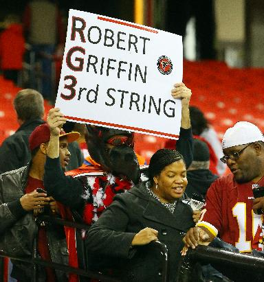 An Atlanta Falcons fan taunts  Washington Redskins fans with a Robert Griffin III sign after the Falcons downed the Redskins 27-26 in an NFL football game on Sunday, Dec. 15, 2013, in Atlanta
