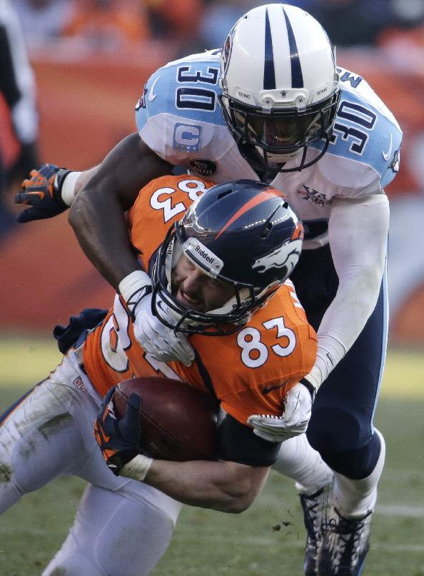 Denver Broncos wide receiver Wes Welker (83) is tackled by Tennessee Titans cornerback Jason McCourty (30) during the first half of an NFL football game on Sunday, Dec. 8, 2013, in Denver