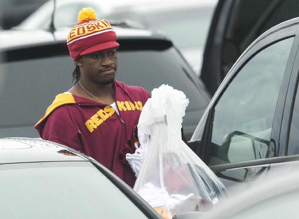 Washington Redskins quarterback Robert Griffin III walks to his car after cleaning out his locker at Redskins Park on Monday, Dec. 30, 2013, in Ashburn, Va. Redskins head coach Mike Shanahan was fired following a 3-13 season