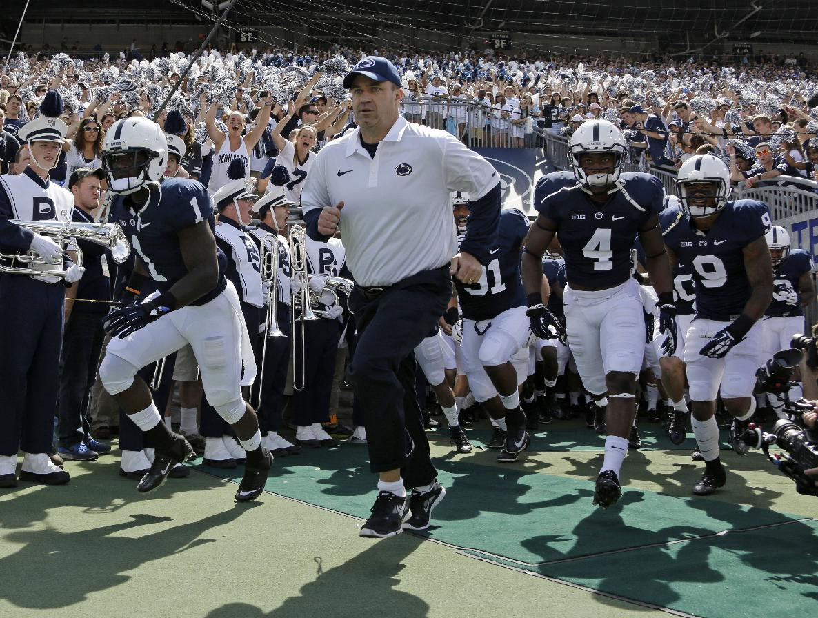 In this Sept. 7, 2013, photo, Penn State coach Bill O' Brien  leads his team onto the field at Beaver Stadium for an NCAA college football game against Eastern Michigan in State College, Pa. Two people familiar with the negotiations say O'Brien has reached an agreement to coach the Houston Texans. The people spoke to The Associated Press on the condition of anonymity because an official announcement hasn't been made