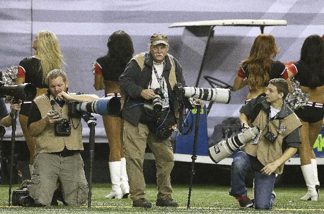In this  Sunday, Dec. 29, 2013, photo, AP Photographer Dave Martin, second from right, works during the first half of an NFL football game between the Carolina Panthers and the Atlanta Falcons, in Atlanta. Martin, a longtime Associated Press photographer based in Montgomery, Ala., died after collapsing on the Georgia Dome field at the Chick-fil-A Bowl on Tuesday, Dec. 31, 2013. Martin was 59