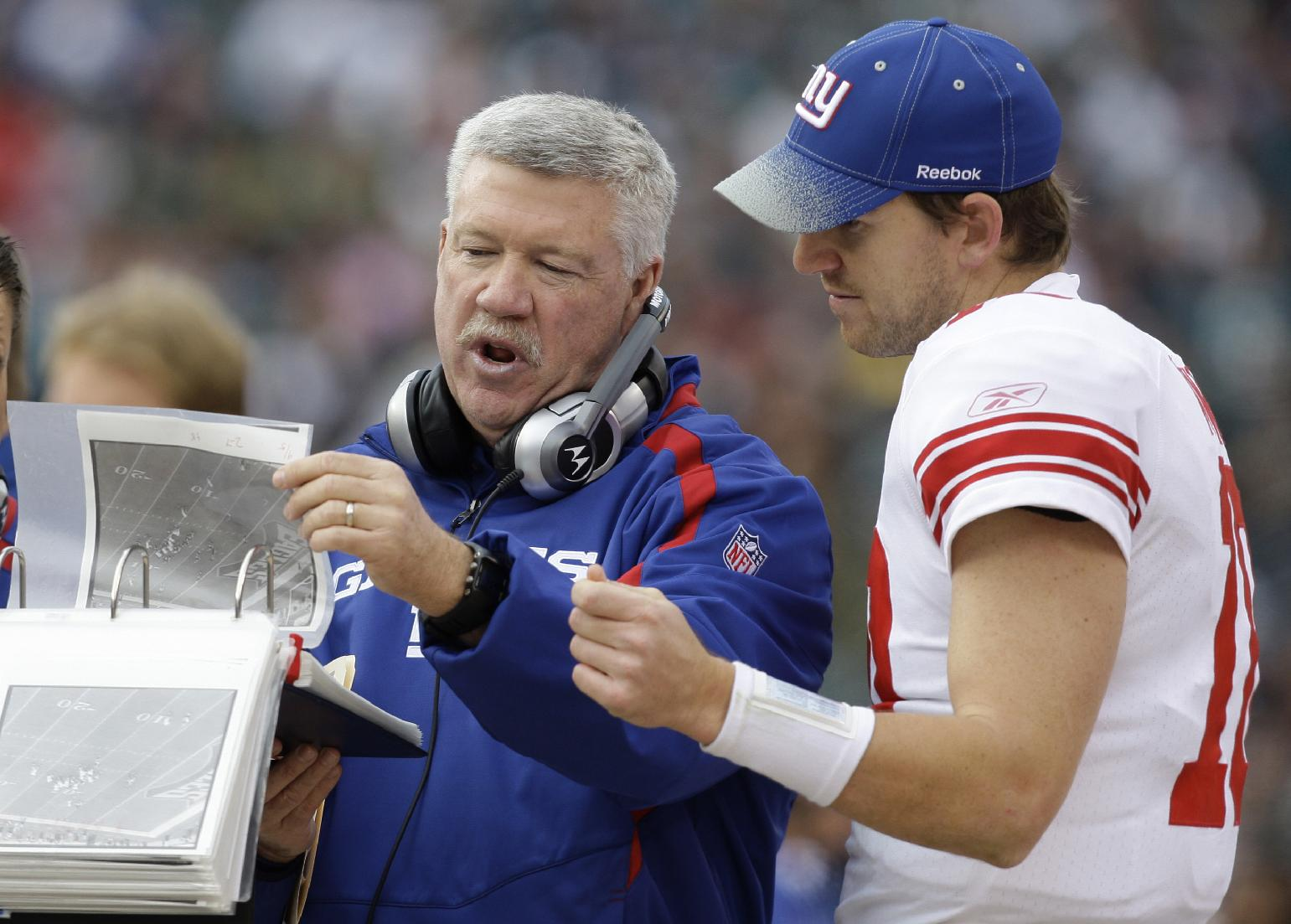 In this Nov. 1, 2009, file photo, New York Giants quarterback Eli Manning (10) goes over game photos with offensive coordinator Kevin Gilbride during an NFL football game against the Philadelphia Eagles in Philadelphia. Gilbride has retired as offensive coordinator for the Giants. The 62-year-old Gilbride, a veteran of 39 years in coaching, said Thursday, Jan. 2, 2014, he wants to devote more time to his family