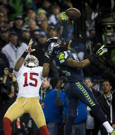CORRECTS BYLINE TO PAUL KITAGAKI JR.-Seattle Seahawks cornerback Richard Sherman (25) hits the ball away from San Francisco 49ers wide receiver Michael Crabtree (15) and is intercepted by Seattle Seahawks outside linebacker Malcolm Smith (53) during the NFL football NFC Championship game, Sunday, Jan. 19, 2014, in Seattle. The Seahawks won 23-17 to advance to the Super Bowl