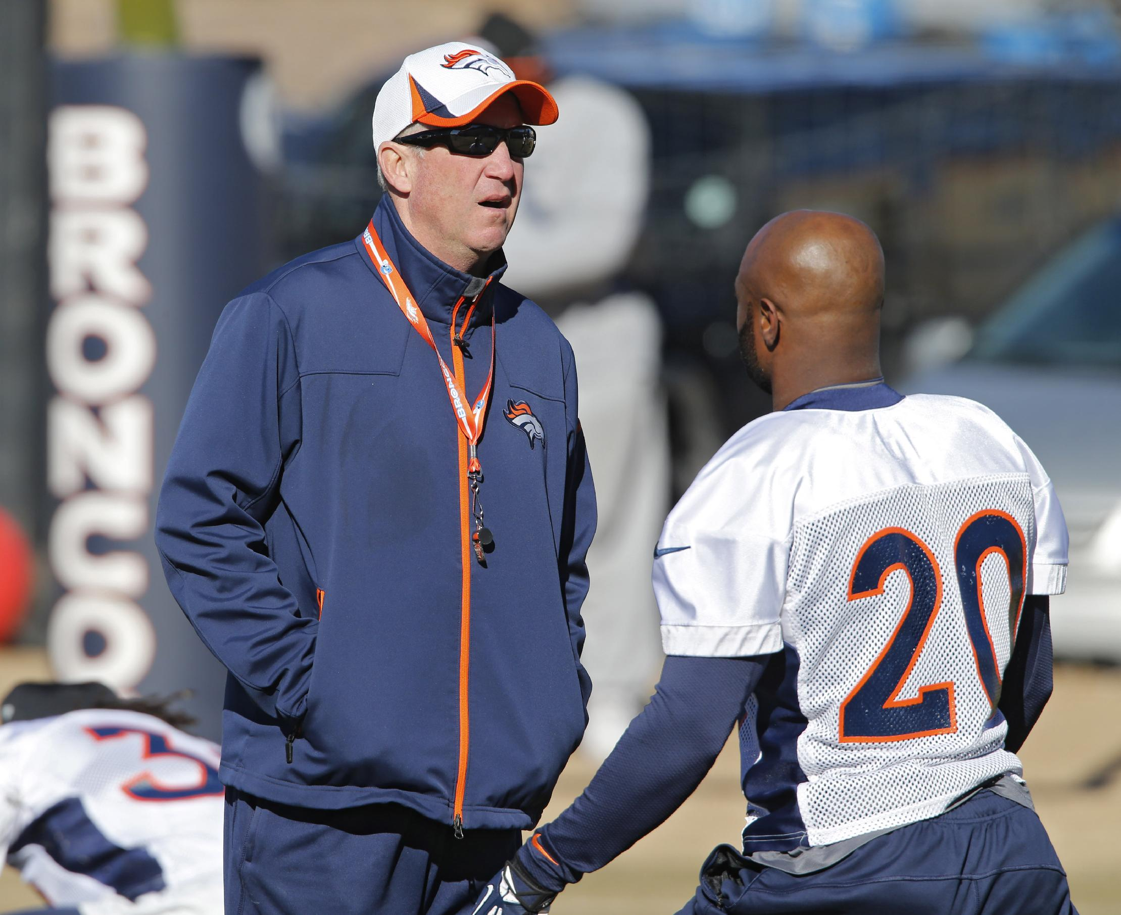 Denver Broncos head coach talks with free safety Mike Adams (20) during NFL football practice at the team's training facility in Englewood, Colo., Saturday, Jan. 25, 2014. The Broncos are scheduled to play the Seattle Seahawks in Super Bowl XLVIII on Feb. 2