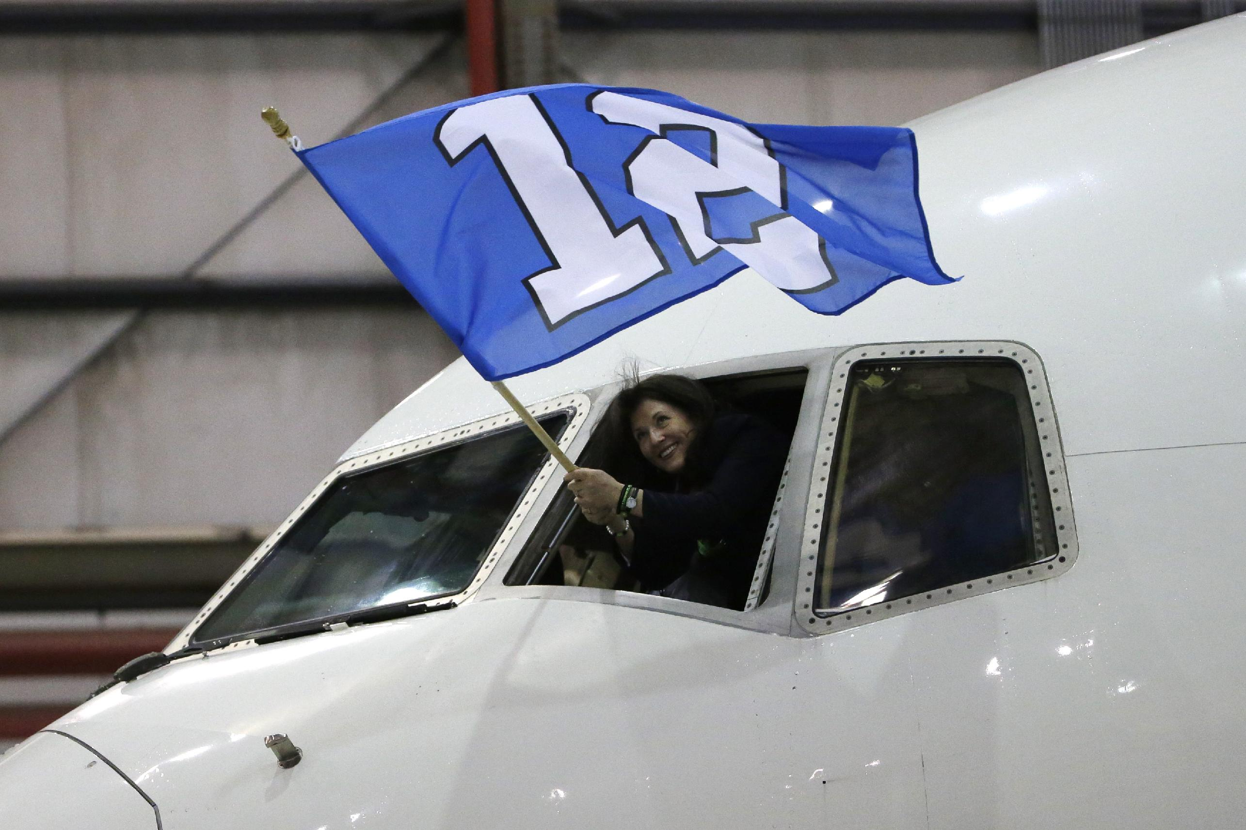 Delta flight attendant Christi Turner waves a flag as the charter plane carrying the Seattle Seahawks arrives at Newark Liberty International Airport for the NFL Super Bowl XLVIII football game, Sunday, Jan. 26, 2014, in Newark, N.J
