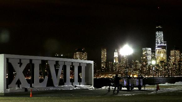 People look at the New York skyline as they stand near the Roman numerals for NFL Super Bowl XLVIII football game at Pier A Park in Hoboken, N.J., Monday, Jan. 27, 2014. The Seattle Seahawks and the Denver Broncos are scheduled to play in the Super Bowl on Sunday, Feb. 2 at MetLife Stadium in East Rutherford, N.J. A concert and fireworks show at Liberty State Park in Jersey City, N.J., kicked off the week festivities leading to Sunday's game