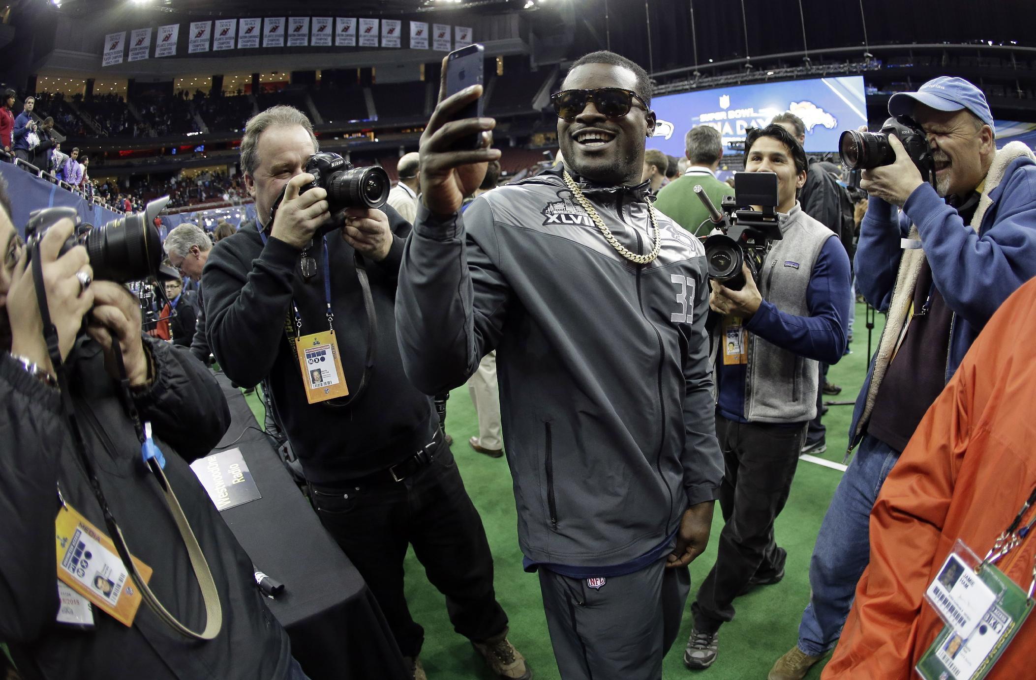 Seattle Seahawks' Christine Michael takes pictures during media day for the NFL Super Bowl XLVIII football game Tuesday, Jan. 28, 2014, in Newark, N.J
