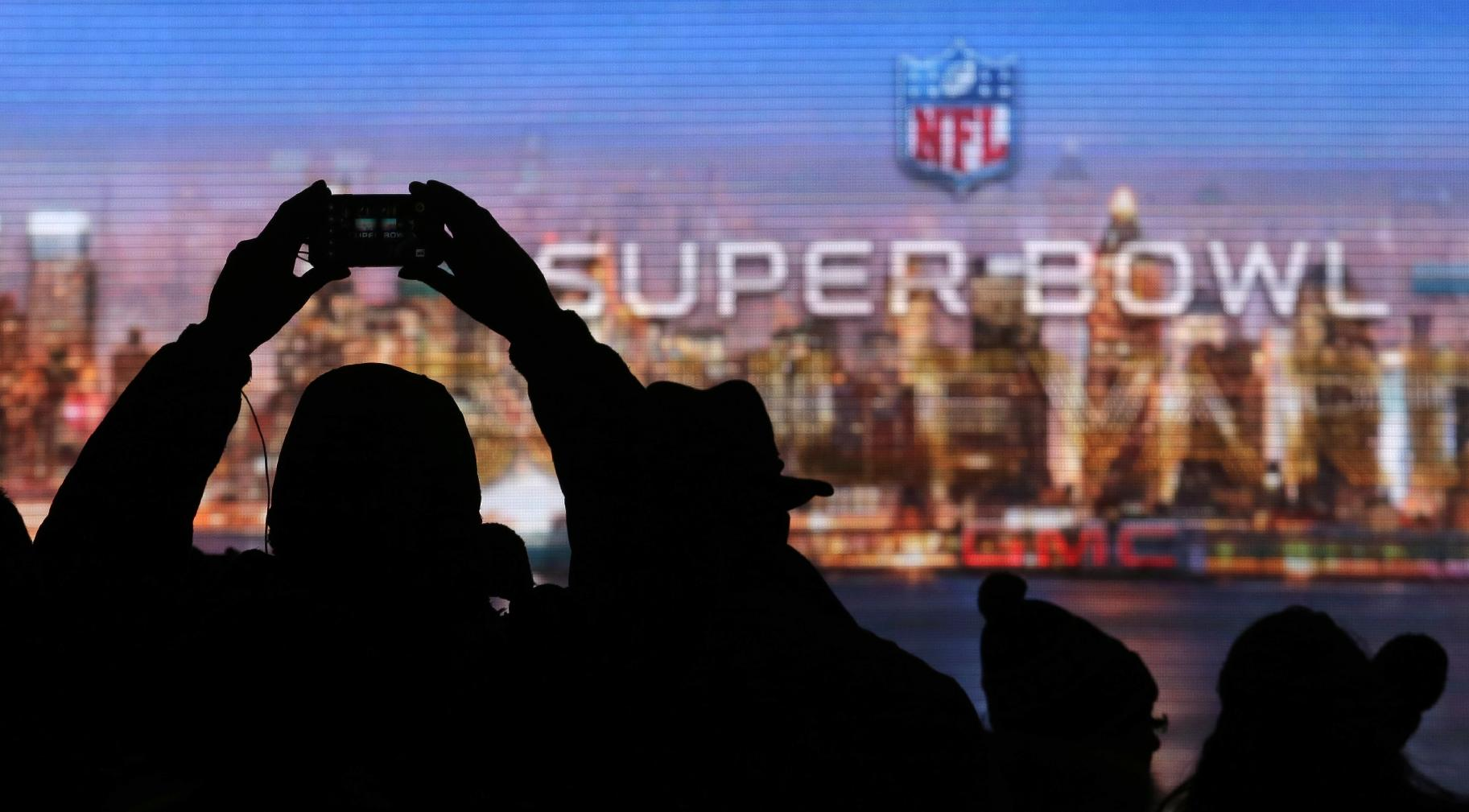 Fans take photos of the Roman numerals for Super Bowl XLVIII on Super Bowl Boulevard Wednesday, Jan. 29, 2014, in New York. The Seattle Seahawks are scheduled to play the Denver Broncos in the NFL Super Bowl XLVIII football game on Sunday, Feb. 2, in East Rutherford, N.J
