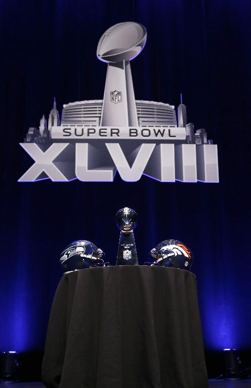 The Vince Lombardi Trophy is displayed between the Seattle Seahawks and the Denver Broncos helmets before a news conference Friday, Jan. 31, 2014, in New York. The Seahawks and the Broncos are scheduled to play in the NFL Super Bowl XLVIII football game on Sunday, Feb. 2, at MetLife Stadium in East Rutherford, N.J