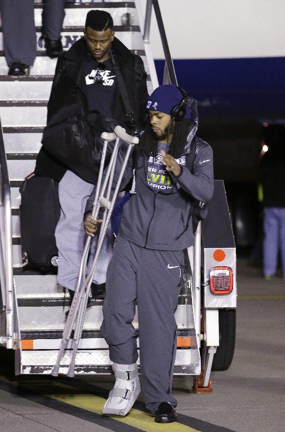 Seattle Seahawks' Richard Sherman carries crutches as he walks down stairs upon the team's arrival Monday, Feb. 3, 2014, at Seattle-Tacoma International Airport in Seattle. The Seahawks beat the Denver Broncos 43-8 in the Super Bowl on Sunday