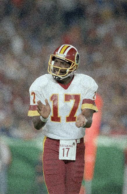 In this Jan. 31, 1988, file photo, Washington Redskins quarterback Doug Williams cheers his team on during the third quarter of the Super Bowl against the Denver Broncos in San Diego. Williams is coming back to the Redskins to work in the front office. The Redskins announced Monday, Feb. 10, 2014, that the quarterback who led the team to the Super Bowl championship in the 1987 season will serve as a personnel executive