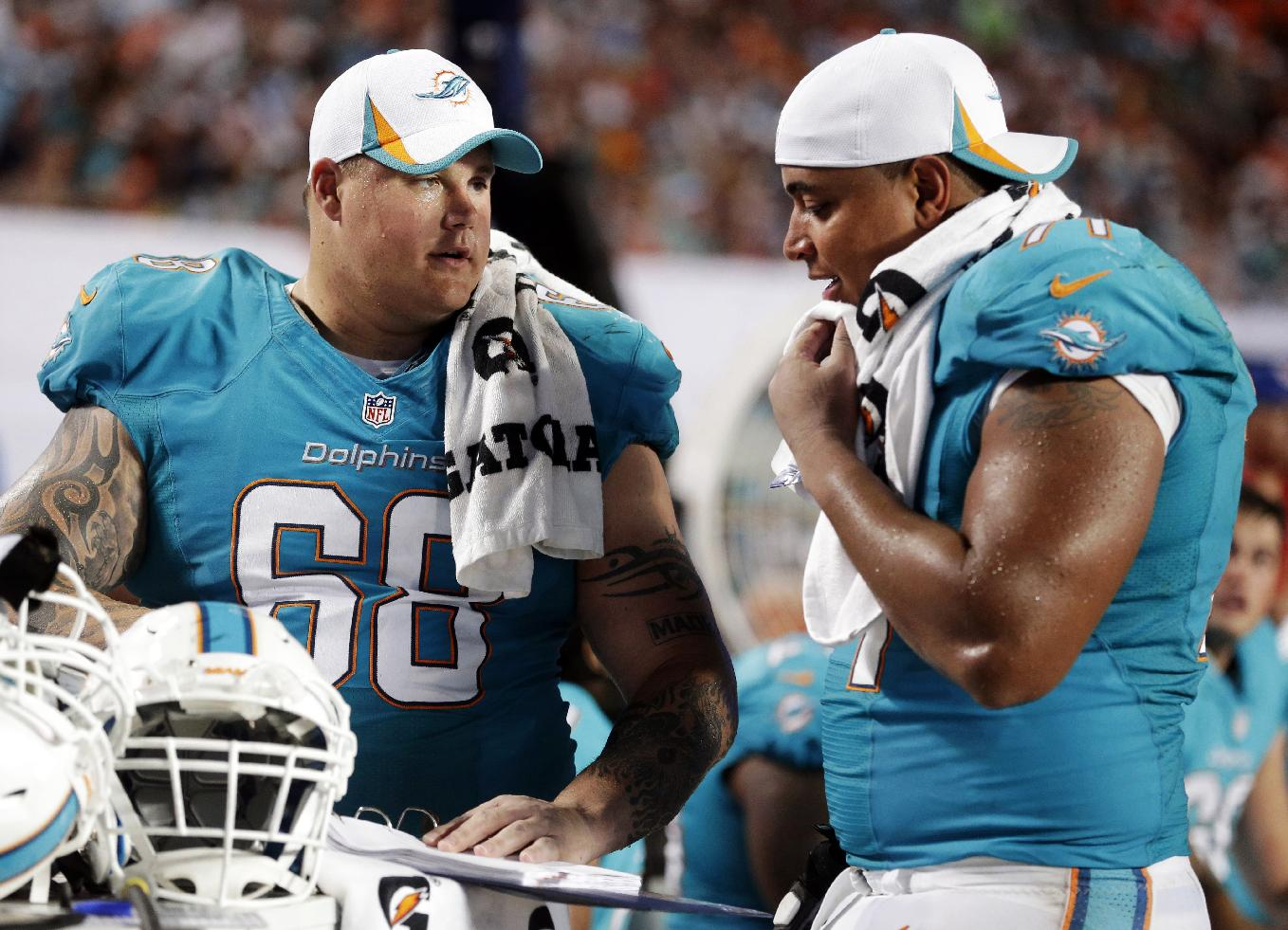 In this Aug. 24, 2013, file photo, Miami Dolphins guard Richie Incognito (68) and tackle Jonathan Martin (71) look over plays during an NFL preseason football game against the Tampa Bay Buccaneers in Miami Gardens, Fla. Martin was subjected to