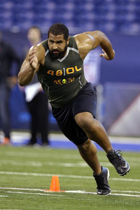 Penn State offensive lineman John Urschel runs a drill at the NFL football scouting combine in Indianapolis, Saturday, Feb. 22, 2014. The all-Big Ten, third-team AP All-American has a Master's degree in math and was awarded the William V. Campbell Trophy as college football's top scholar-athlete