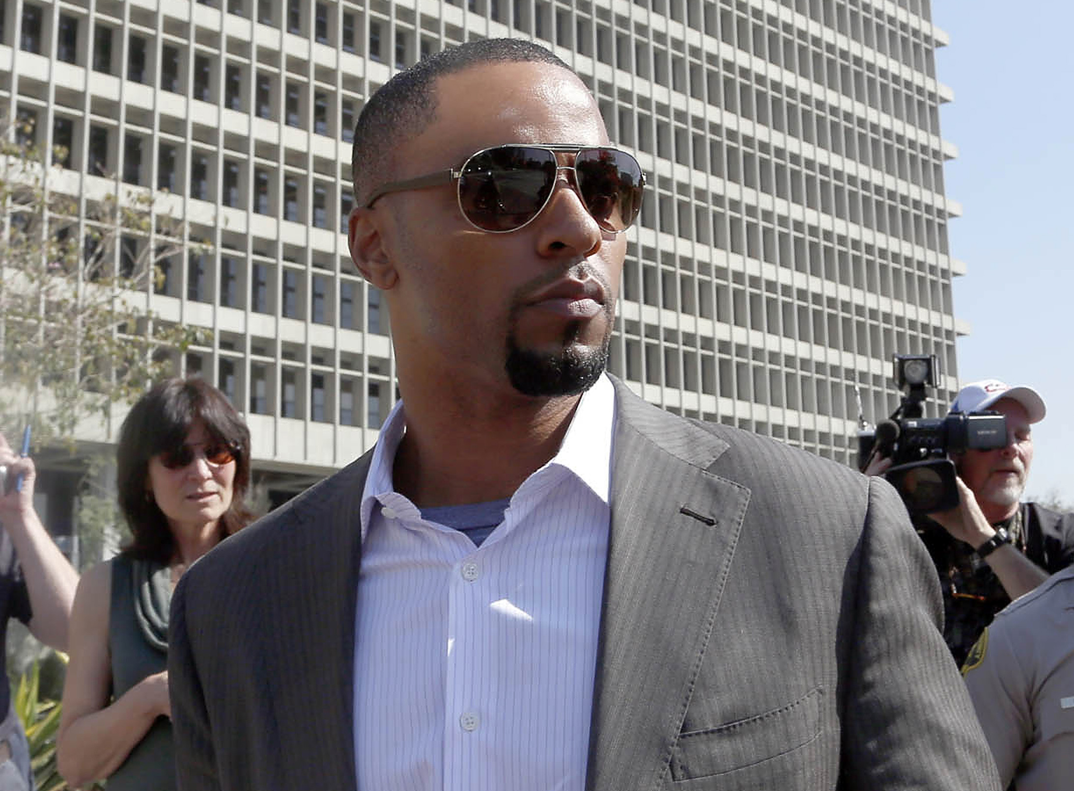 In this Feb. 14, 2014, photo, former NFL safety Darren Sharper leaves a courthouse in Los Angeles. An arrest warrant has been issued for Sharper and another man, accusing them of raping two women in New Orleans last year. Sharper also is under investigation in sexual assault cases in Florida, Nevada and Arizona and has pleaded not guilty to rape charges in Los Angeles