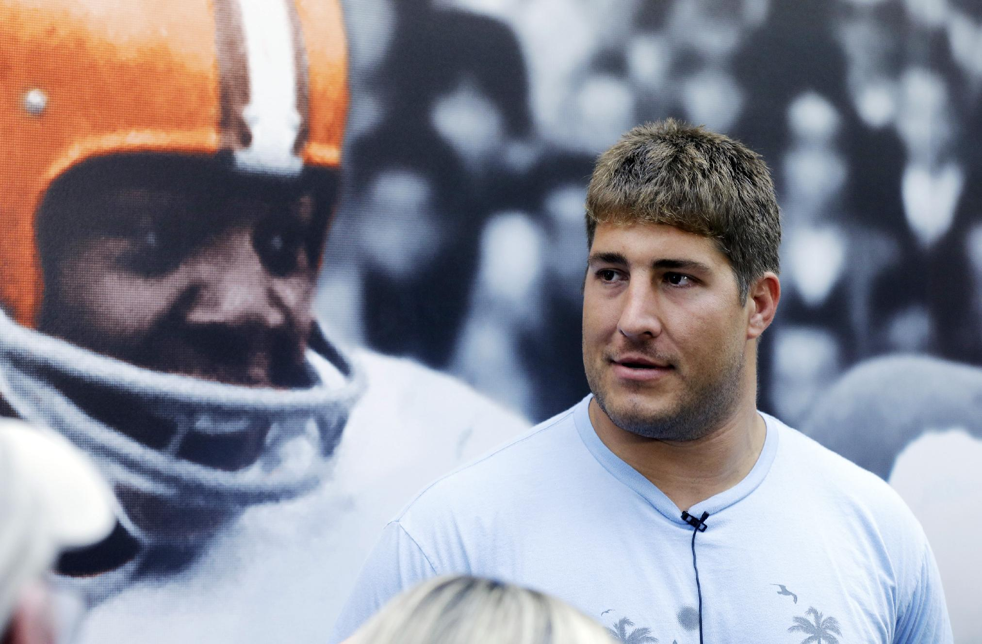 Cleveland Browns center Alex Mack talks with the media in front of a large mural of Hall of Fame running back Jim Brown at the NFL football team's facility in Berea, Ohio, Monday, April 14, 2014. The Pro Bowl center was one step out the door from leaving the Browns last week, but following a muddled free agency courtship, he's staying in Cleveland after the Browns matched the Jacksonville Jaguars contract offer