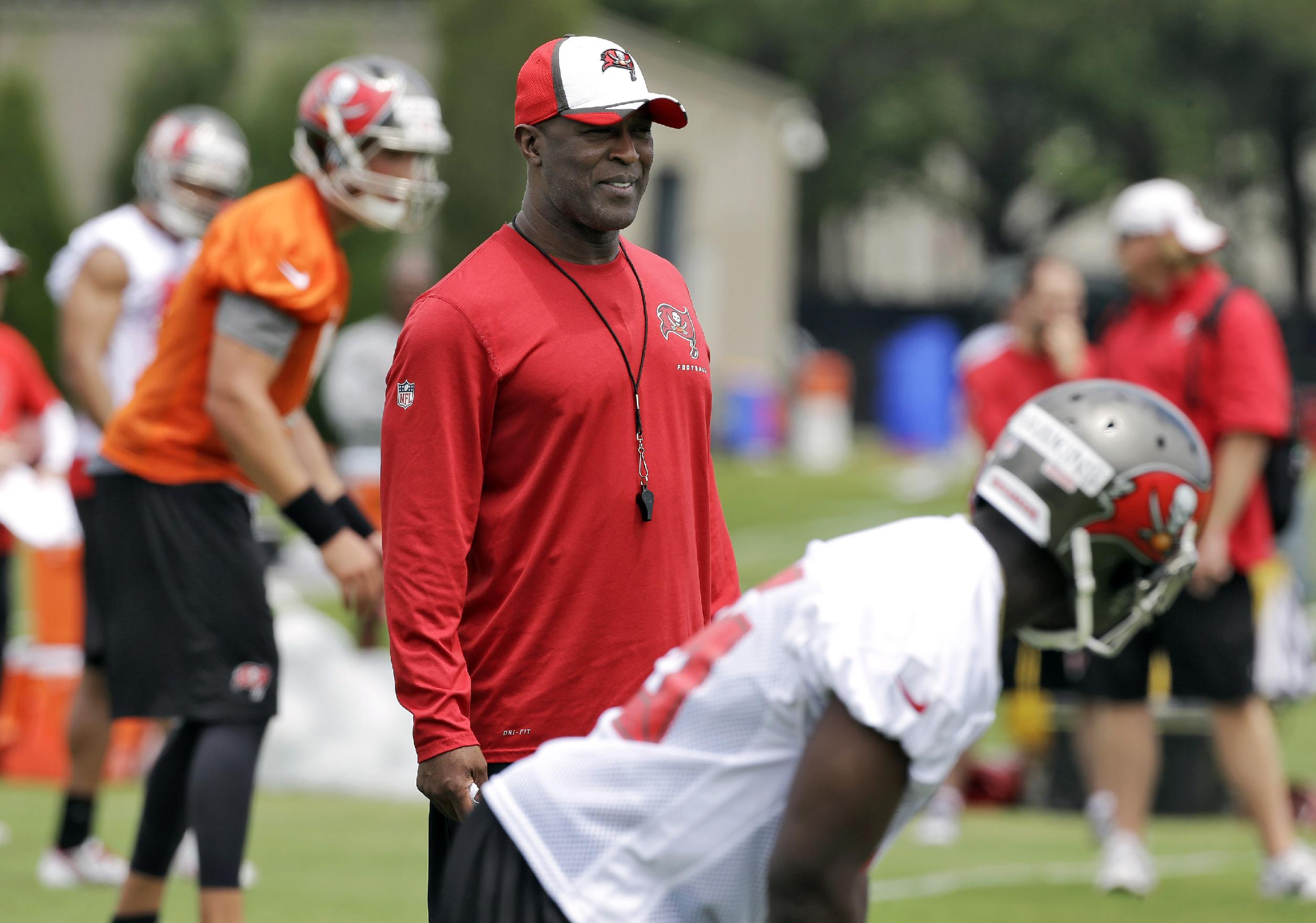 New Tampa Bay Buccaneers head coach Lovie Smith, center, stands during voluntary minicamp football practice Tuesday, April 22, 2014, in Tampa, Fla