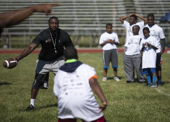 Kevin Burnett, linebacker for the Raiders, leads a group of children through drills during a football camp put on by LaMarr Woodley at Saginaw High School, Saturday, June 14, 2014