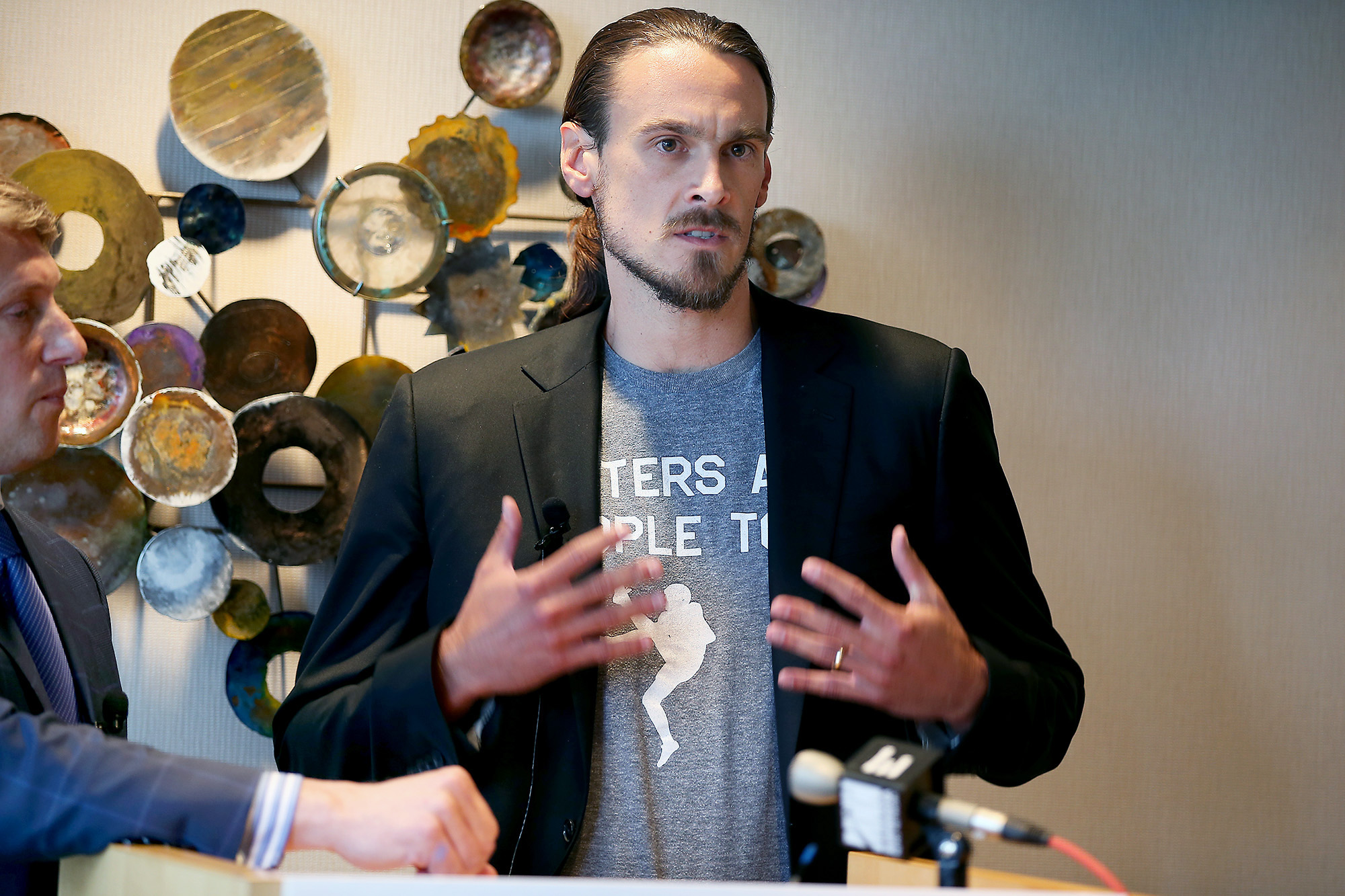 Former Minnesota Vikings punter Chris Kluwe, right, speaks during a press conference, Tuesday, July 15, 2014 in Minneapolis, Minn. Former Minnesota Vikings punter Chris Kluwe intends to sue the team over allegations of anti-gay conduct by a coach, his lawyer said Tuesday