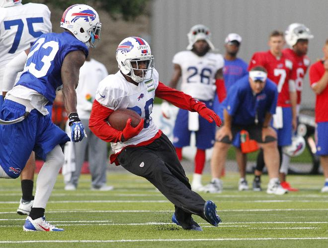 Buffalo Bills running back C.J. Spiller (28) runs past safety Aaron Williams (23) during their NFL football training camp in Pittsford, N.Y., Sunday, July 20, 2014