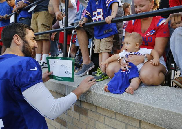 Buffalo Bills punter Jake Dombrowski (4) greets Jace Phillips, 8 months, of Palmyra, N.Y., on the opening night of their NFL football training camp in Pittsford, N.Y., Sunday, July 20, 2014