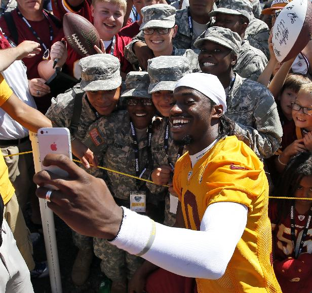 Washington Redskins quarterback Robert Griffin III takes a selfie with U.S. Army soldiers with Bravo Co. of the 244th Quartermaster Battalion from Fort Lee, Va., after practice at the team's NFL football training facility, Friday, July 25, 2014 in Richmond, Va. (AP Photo)