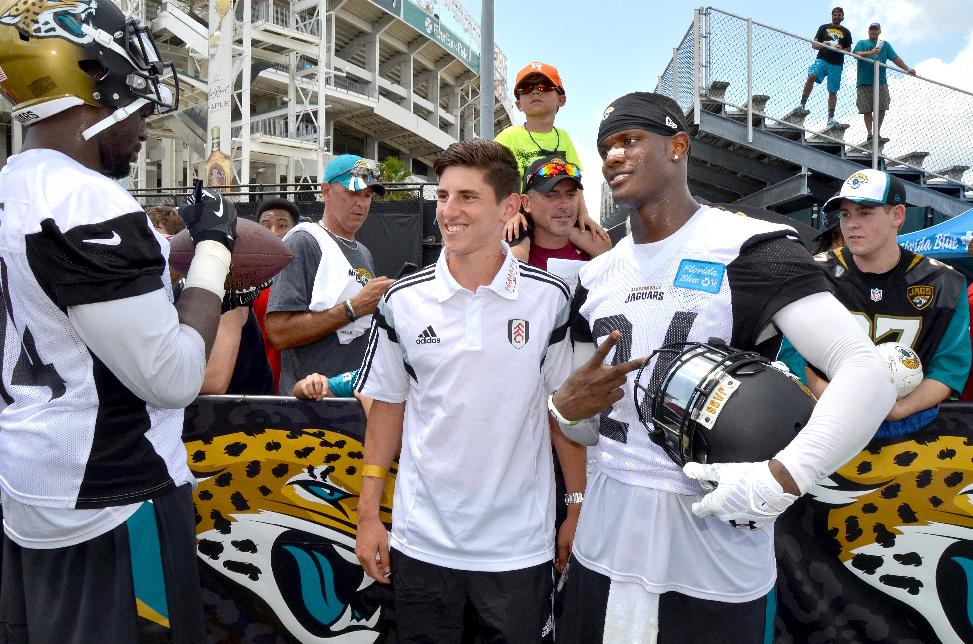 Emerson Hyndman, center, an American who plays for Fulham, has his picture taken with the Jacksonville Jaguars' Will Blackmon (24) after the NFL team's football training camp, on Friday, July 25, 2014, in Jacksonville, Fla