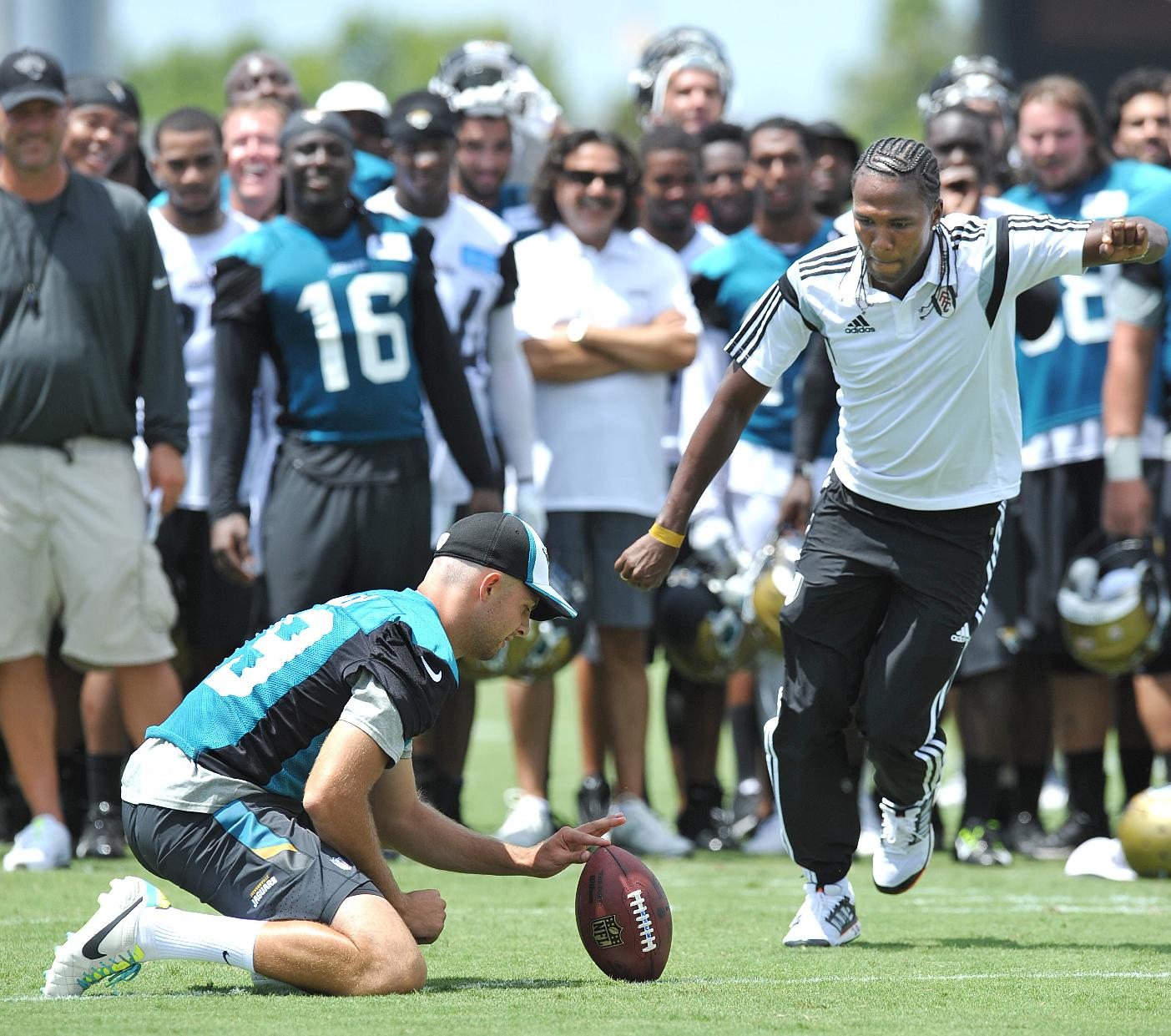Jacksonville Jaguars' punter Bryan Anger, left, holds the ball as Hugo Rodallega, of the Fulham Football Club, kicks a field goal after the NFL team's football training camp, on Friday, July 25, 2014, in Jacksonville, Fla