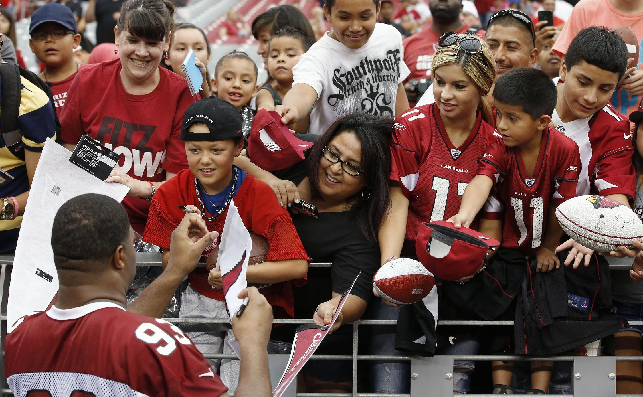 Arizona Cardinals' Calais Campbell, left, signs autographs for fans after the first day of the NFL football team's training camp Saturday, July 26, 2014, in Glendale, Ariz