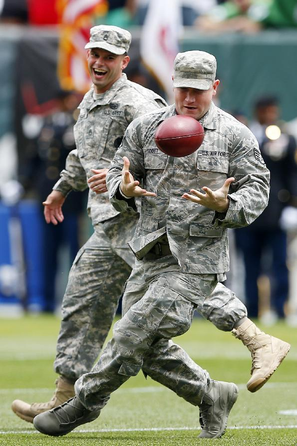 Members of the military go for a pass thrown by Philadelphia Eagles long snapper Jon Dorenbos during NFL football training camp Monday, July 28, 2014, in Philadelphia