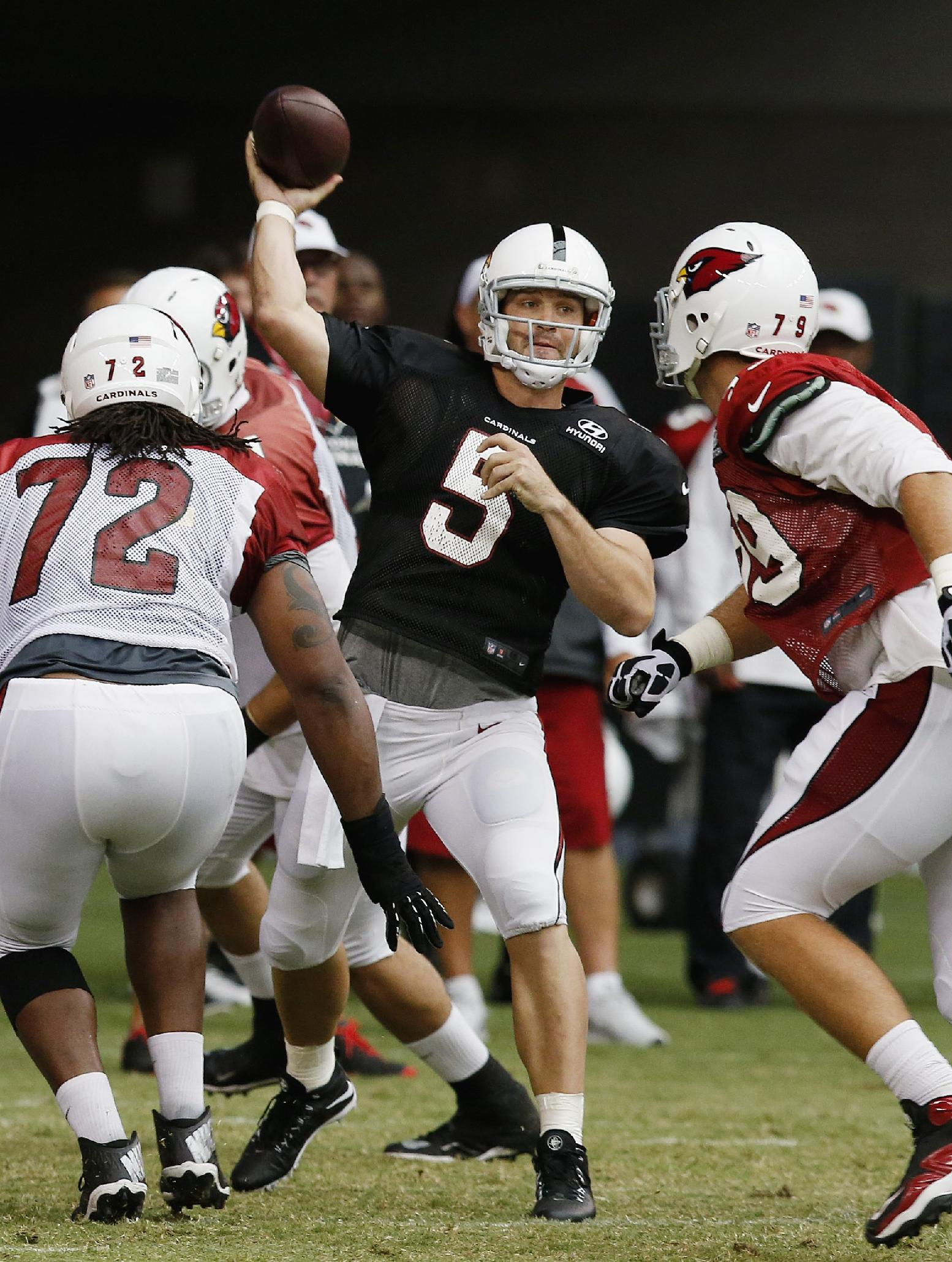 Arizona Cardinals' Drew Stanton (5) makes a throw as Ed Stinson (72) and Bradley Sowell (79) both look on during NFL football training camp practice on Wednesday, July 30, 2014, in Glendale, Ariz