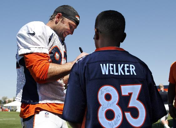 Denver Broncos' Wes Welker signs an autograph for a fan following NFL football training camp on Tuesday, Aug 12, 2014, in Englewood, Colo