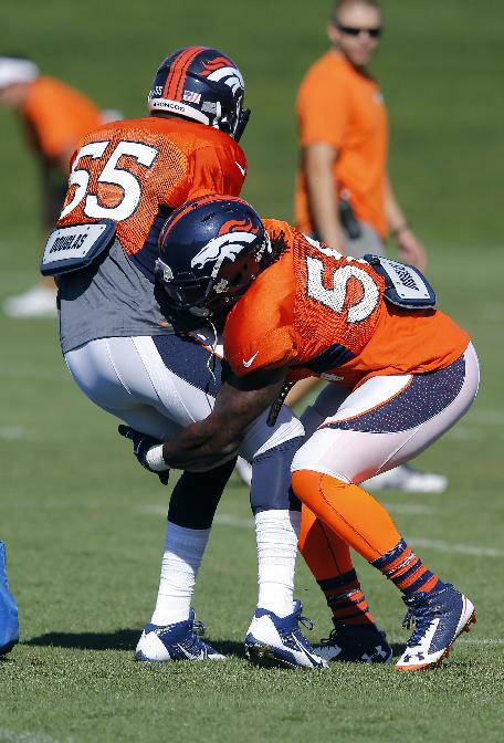 Denver Broncos' Danny Trevathan runs a drill against Lerentee McCray (55) during NFL football training camp on Tuesday, Aug 12, 2014, in Englewood, Colo.  Trevathan was injured later in practice