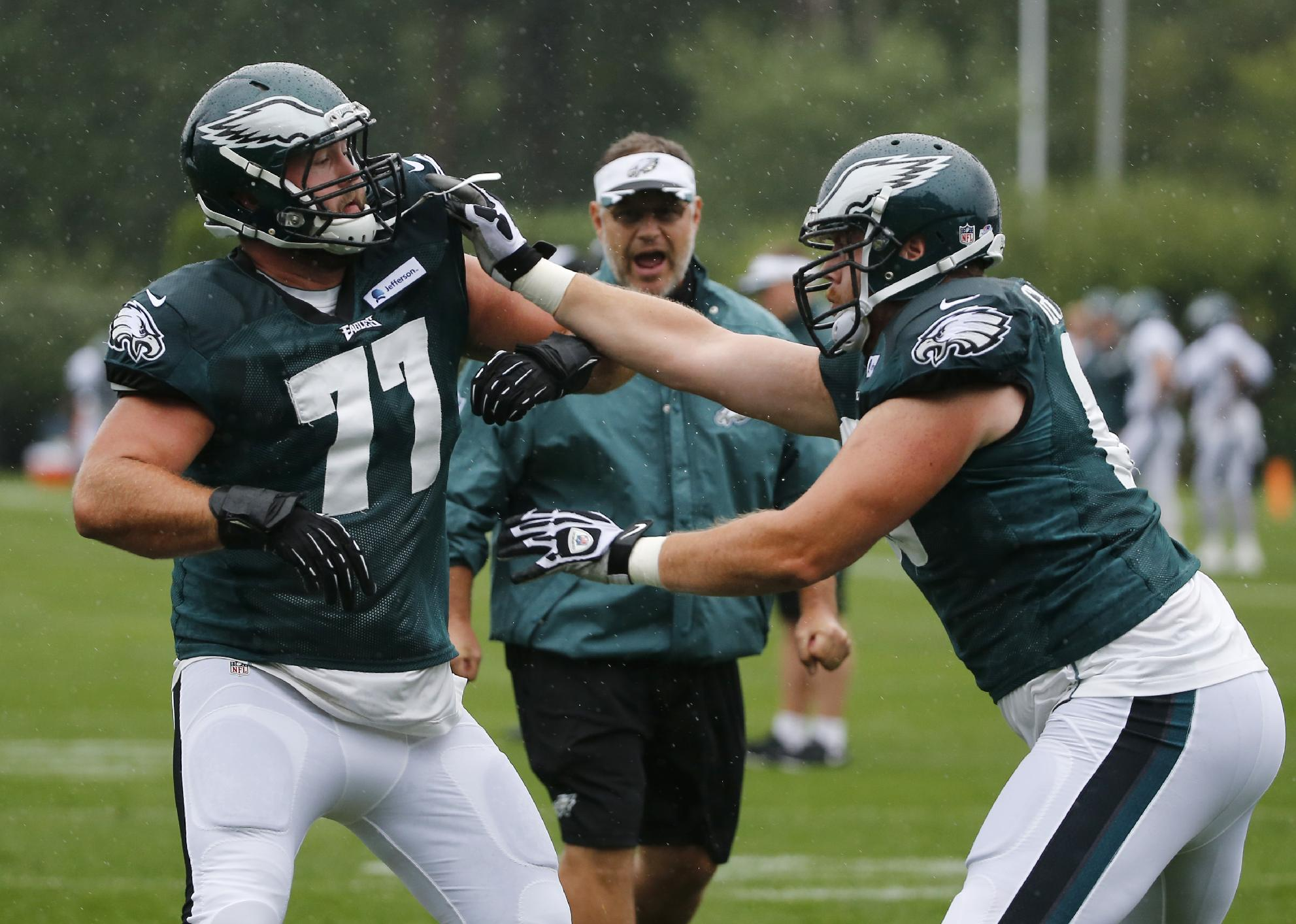 Philadelphia Eagles tackle Andrew Gardner, right, pushes against tackle Kevin Graf (77) as offensive line coach Jeff Stoutland yells instruction during an NFL football training camp joint practice of the New England Patriots and the Philadelphia Eagles in Foxborough, Mass., Wednesday, Aug. 13, 2014