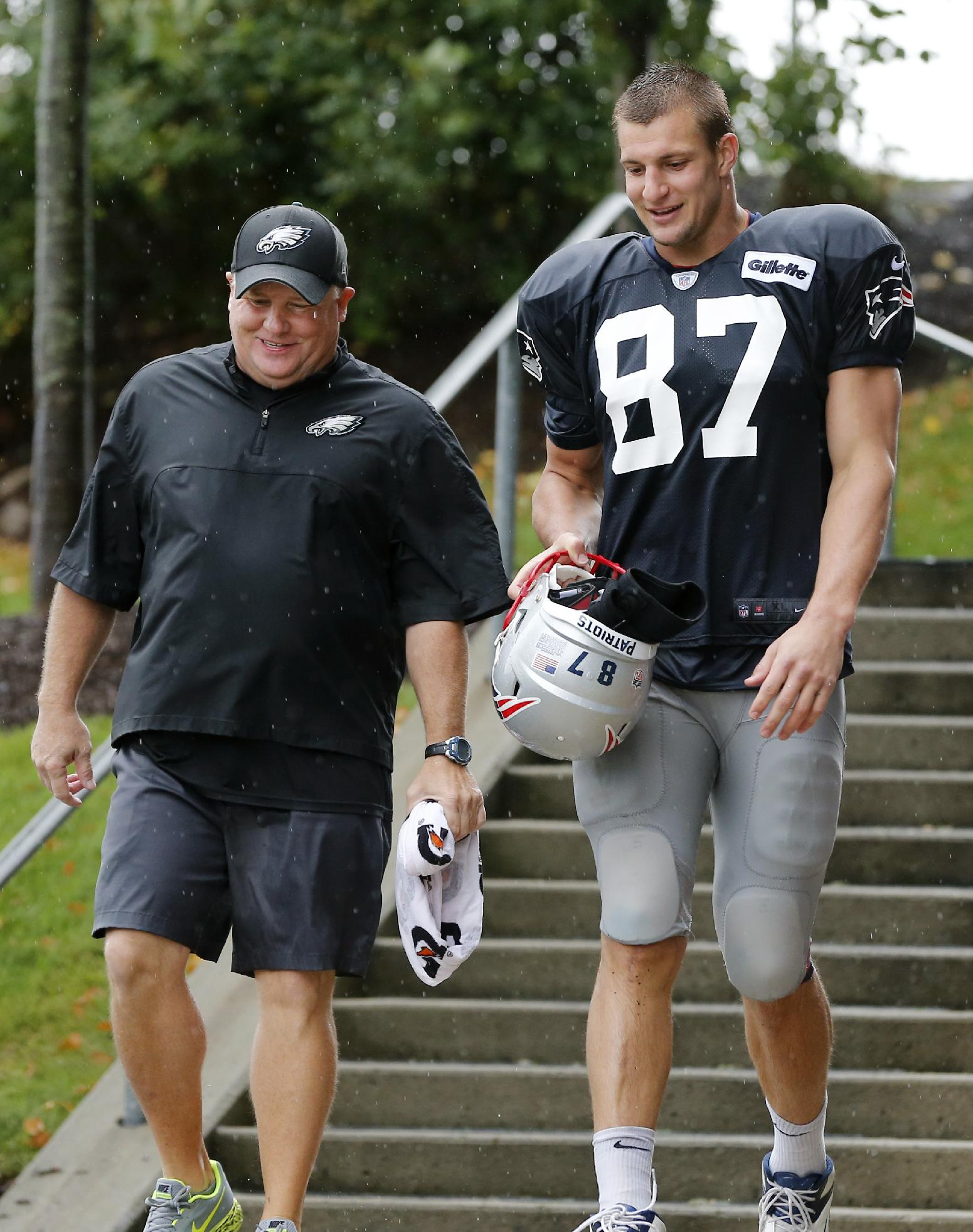 Philadelphia Eagles head coach Chip Kelly and New England Patriots tight end Rob Gronkowski (87) chat as they leave a joint NFL football training camp practice in Foxborough, Mass., Wednesday, Aug. 13, 2014