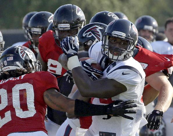 Houston Texans running back Alfred Blue, right, is wrapped up by the Atlanta Falcons defense including free safety Dwight Lowery (20) during an NFL football training camp practice Wednesday, Aug. 13, 2014, in Houston. The Falcons are practicing with the Houston Texans this week before their preseason game Saturday
