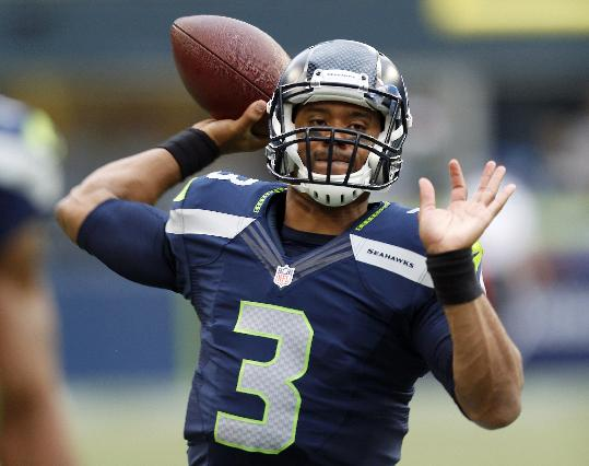 Seattle Seahawks quarterback Russell Wilson passes during warm-ups before a preseason NFL football game against the San Diego Chargers, Friday, Aug. 15, 2014, in Seattle
