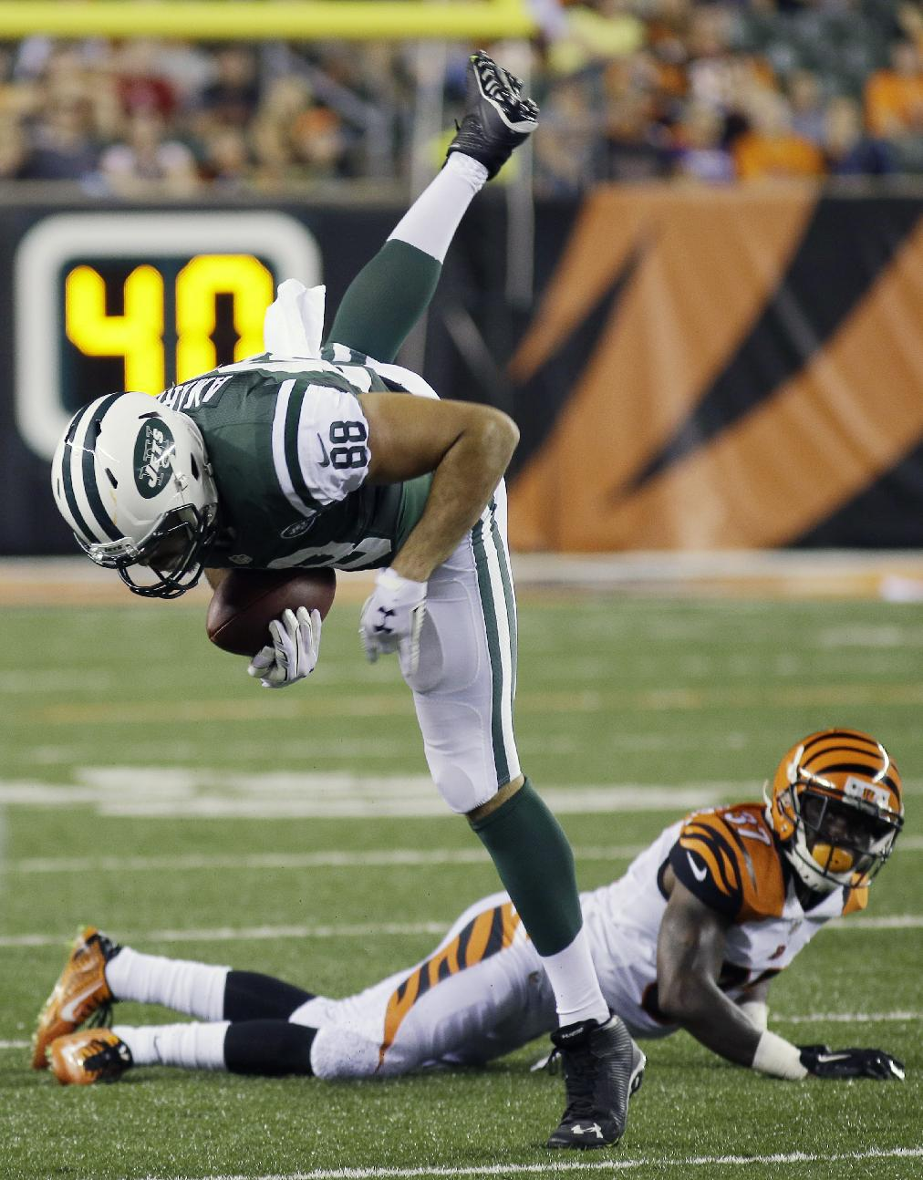 New York Jets tight end Jace Amaro (88) is tripped up by Cincinnati Bengals cornerback Chris Lewis-Harris in the second half of an NFL preseason football game, Saturday, Aug. 16, 2014, in Cincinnati