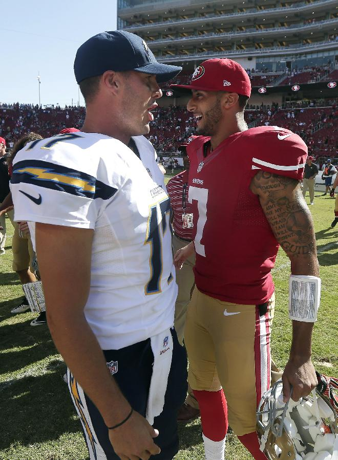 San Diego Chargers quarterback Philip Rivers, left, talks with San Francisco 49ers quarterback Colin Kaepernick (7) after an NFL preseason football game in Santa Clara, Calif., Sunday, Aug. 24, 2014. The 49ers won 21-7