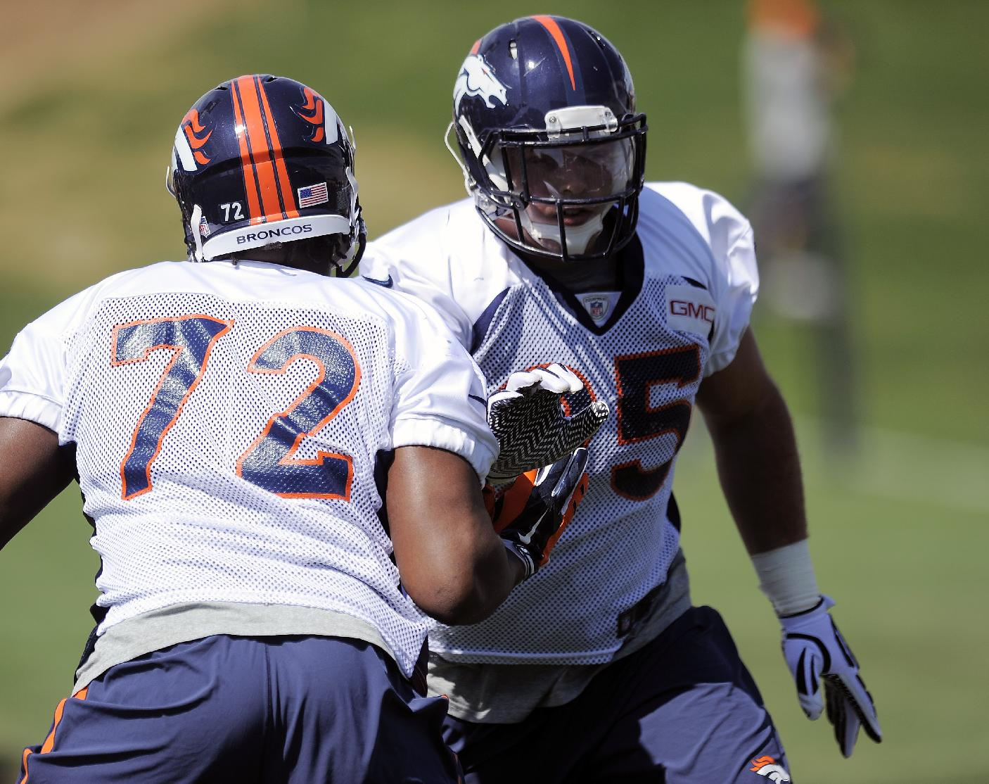 Denver Broncos defensive end Brian Sanford, left, and Denver Broncos defensive end Derek Wolfe, right, run a drill at NFL football practice in Englewood, Colo., on Monday, Aug. 25, 2014