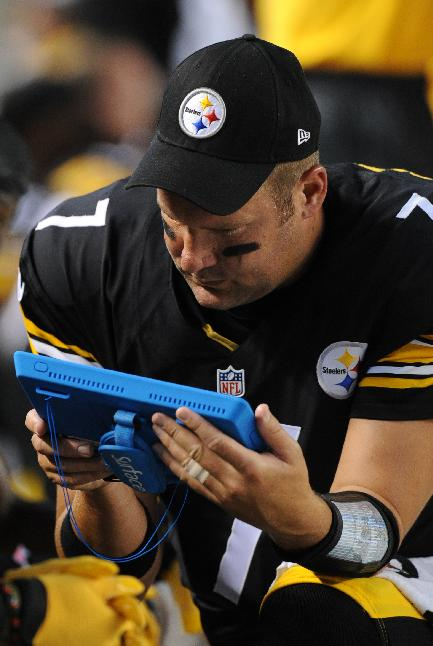 In this Aug. 16, 2014, file photo, Pittsburgh Steelers quarterback Ben Roethlisberger (7) looks over one of the new tablets teams are using on the sideline during the first half of the NFL football preseason game against the Buffalo Bills in Pittsburgh. The NFL and its partners have been ahead of the curve in technology on television, but coaches were stuck using antiquated photo prints and cardboard play sheets. This season, coaches have the option of using NFL-approved tablets during games
