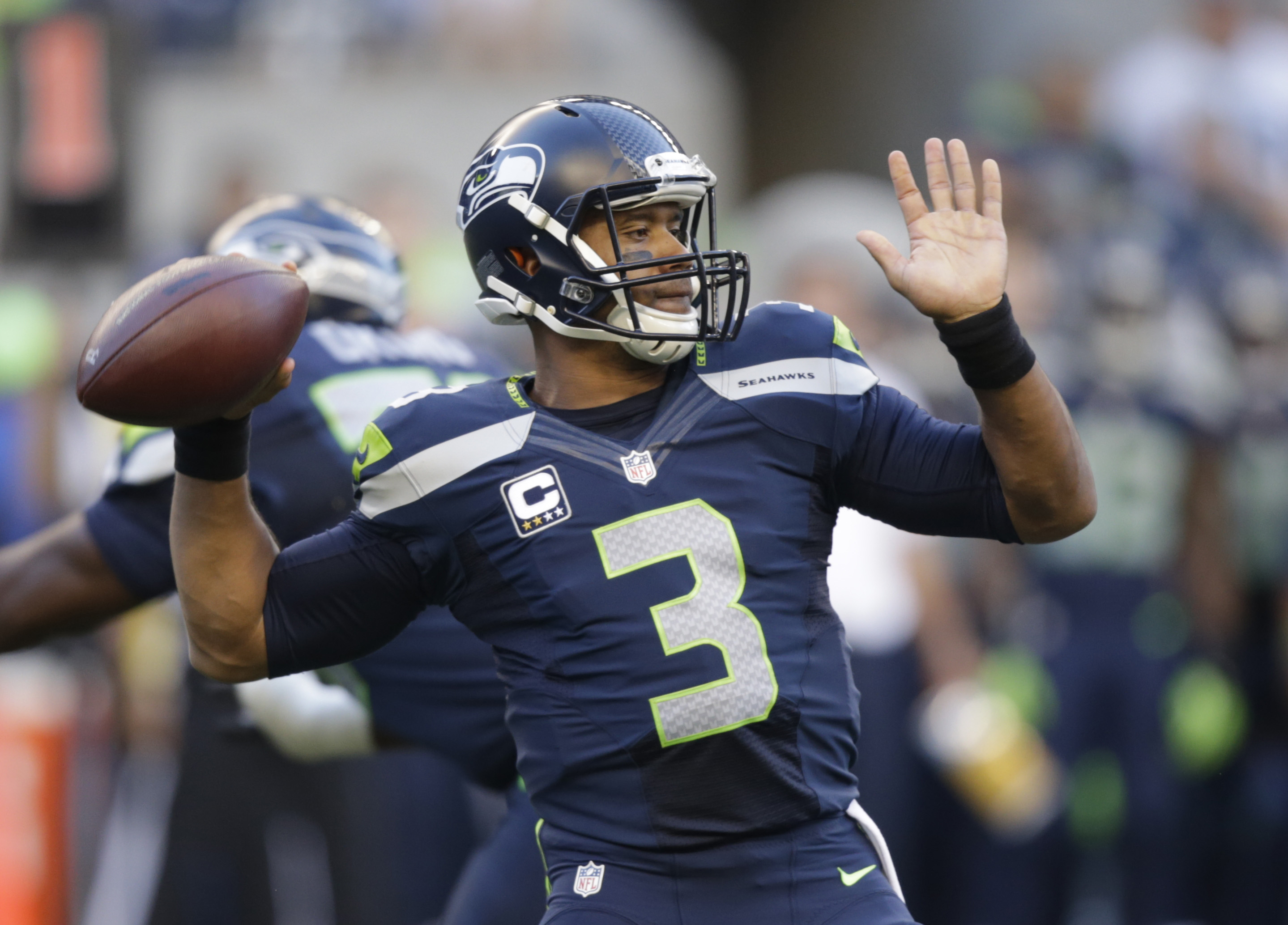 Seattle Seahawks quarterback Russell Wilson winds up to pass against the Green Bay Packers in the first half of an NFL football game, Thursday, Sept. 4, 2014, in Seattle