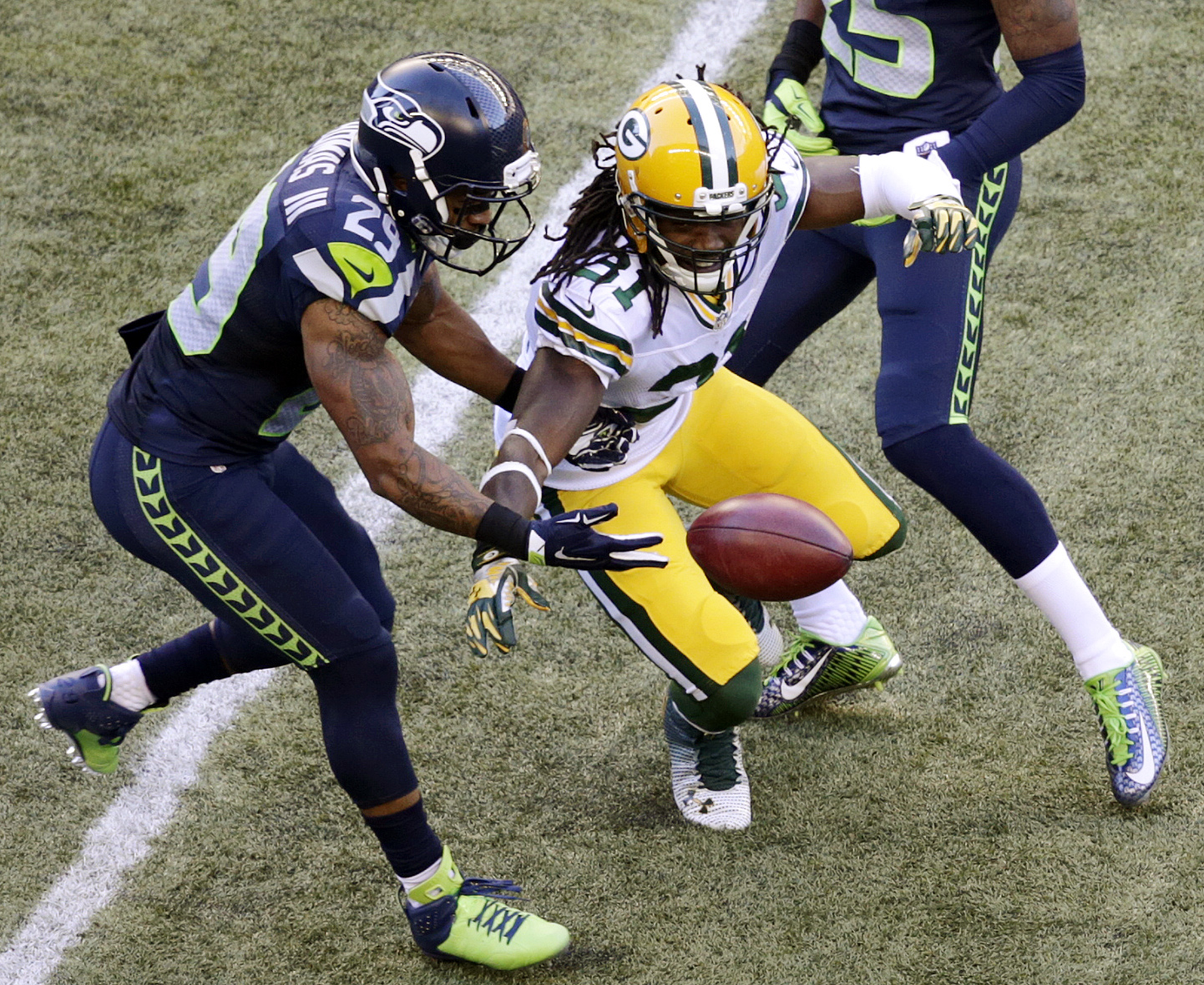 Seattle Seahawks' Earl Thomas, left, muffs the catch on a punt as Green Bay Packers' Davon House reaches for the ball in the first half of an NFL football game, Thursday, Sept. 4, 2014, in Seattle. The Seahawks got possession