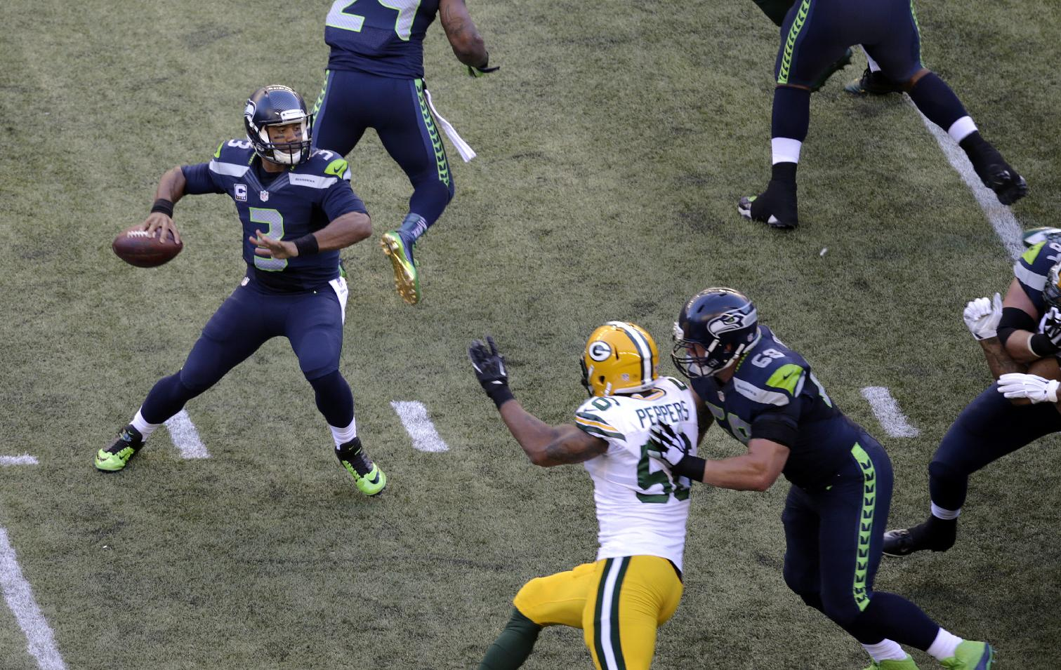 Seattle Seahawks quarterback Russell Wilson (3) looks to pass against the Green Bay Packers during the first half of an NFL football game, Thursday, Sept. 4, 2014, in Seattle