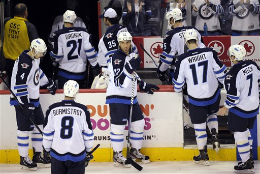 Winnipeg Jets right wing Chris Thorburn (22), Paul Postma (4) and Alex Burmistrov (8), of Russia, look on as they leave the ice after losing 5-3 to the Washington Capitals in an NHL hockey game, Tuesday, April 23, 2013, in Washington. Jets defenseman Derek Meech (7), James Wright (17), Mark Stuart (5), Al Montoya (35) and Aaron Gagnon (21) also head off the ice