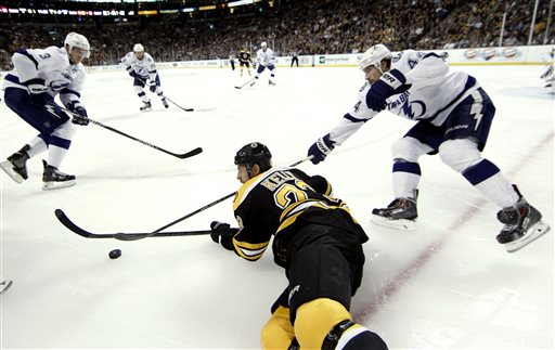 Boston Bruins' Chris Kelly tries to control the puck from the ice as Tampa Bay Lightning's Nate Thompson (44) and Keith Aulie (3) move in during the third period of Boston's 2-0 win in an NHL hockey game in Boston, Thursday, April 25, 2013