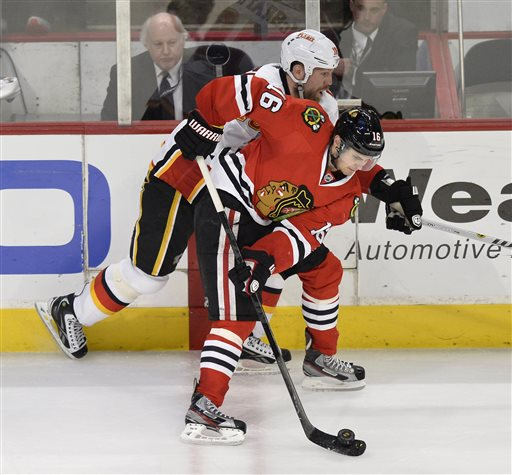 Chicago Blackhawks' Marcus Kruger of Sweden, front, controls the puck as Calgary Flames' Brian McGrattan defends during the third period of an NHL hockey game, Friday, April 26, 2013 in Chicago. The Blackhawks won 3-1.