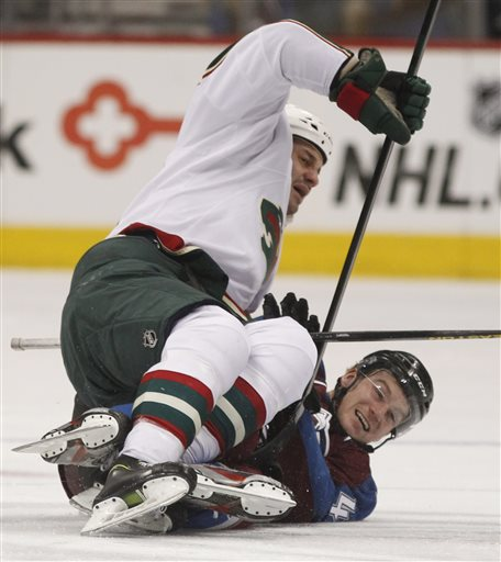 Minnesota Wild center Zenon Konopka, top, lands on top of Colorado Avalanche center Brad Malone after battling for the puck in the second period of an NHL hockey game in Denver on Saturday, April 27, 2013.